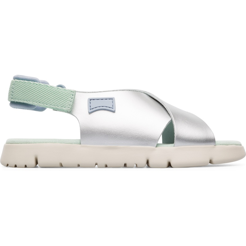 Camper Oruga, Sandals Kids, Grey , Size 25 (US), K800163-007 - Main material: Smooth satin leather Color: silver Lightweight. Leather Working Group Certified Padded Insole: soft feeling and cushioning Velcro Lining: 55 % Fabric (60% Nylon - 40% PU) 39 % Calfskin finished rubberized 6 % Nylon - These silver childrens sandals combine clean and contemporary design with careful detailing, making them perfect to wear every day. The uppers are made of smooth satin leather with a special coating which means they can be easily cleaned. Velcro heel straps make them easy-fitting while interior padding gives an extra-soft feeling and cushions the feet. The sandals are extraordinarily lightweight thanks to their 100% EVA outsoles, which feature flex-cuts for that added flexibility.