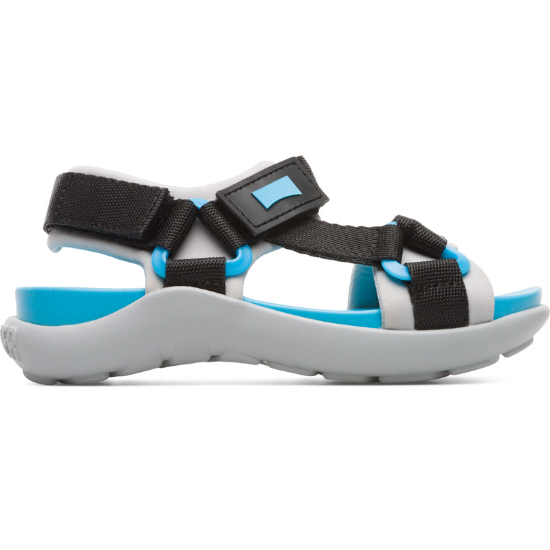 Camper Wous, Sandals Kids, Black/Grey, Size 25 (US), K800360-002 - Upper: Technical fabric (Nylon) Color: Black / Blue / gray Outsole/Features: Rubber for good grip Velcro straps for easy fit Waterfriendly for easy cleaning Insole: Anatomic PU for natural foot-shape fit Lining: 59% PU 38% Fabric (60% Polyester - 35% Nylon - 5% Spandex) 3% Fabric (60% Polyester - 35% Nylon - 5% Spandex) - Kids multi-colored sandal with rubber outsole and Velcro straps. Black and blue details. Designed for both land and water activities, Wous is made from protective leather and boasts a unique design for every summer endeavor.